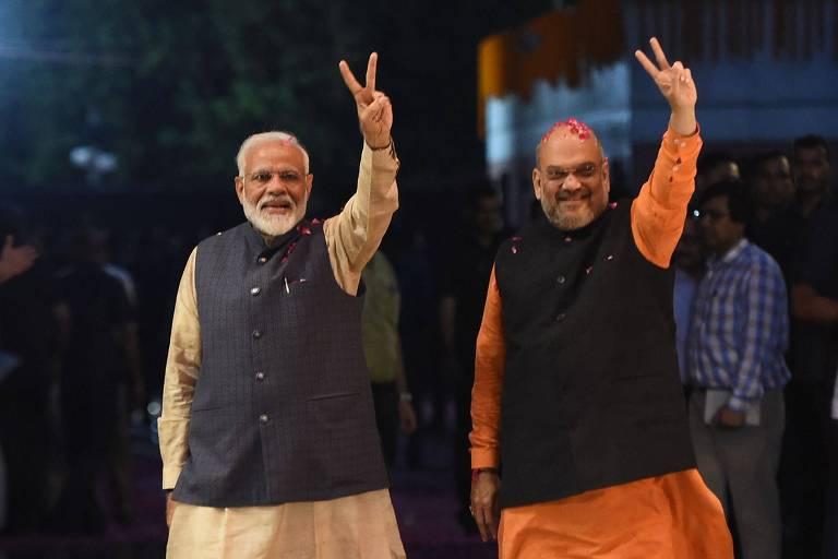 O premiê da Índia, Narendra Modi, à esq., ao lado de Amit Shah, presidente de seu partido, o BJP, acena para apoiadores em Nova Déli