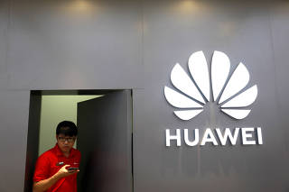 A staff uses a phone as he works at Huawei Flagship Store in Bangkok