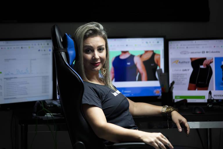 Mulher sentada em frente a três telas de computador que mostram artigos esportivos