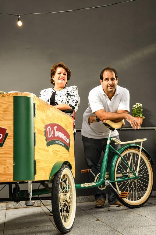 Homem e mulher atrás de bicicleta que puxa um carrinho