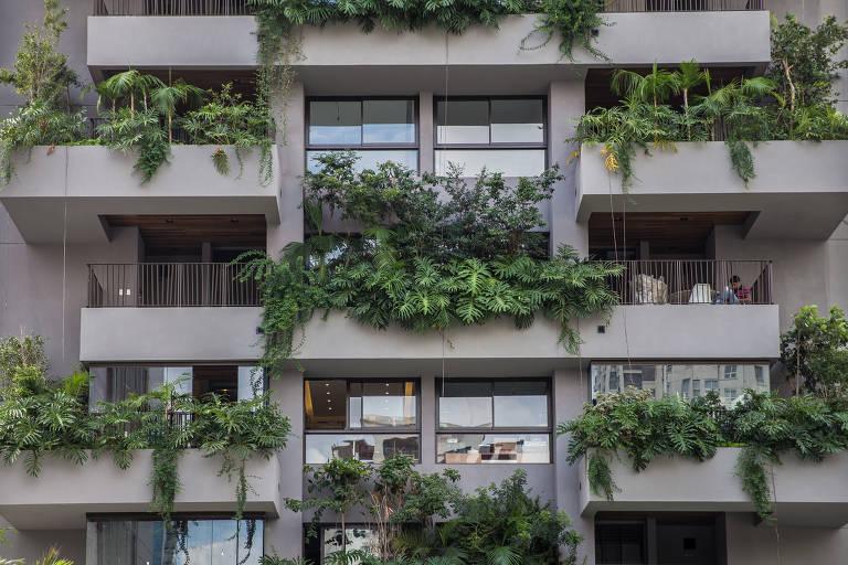 Sacadas de prédio com muitas plantas em cada uma delas