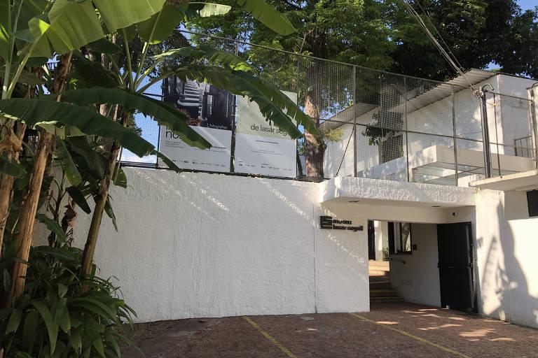Fachada branca, com plantas na frente e calçada