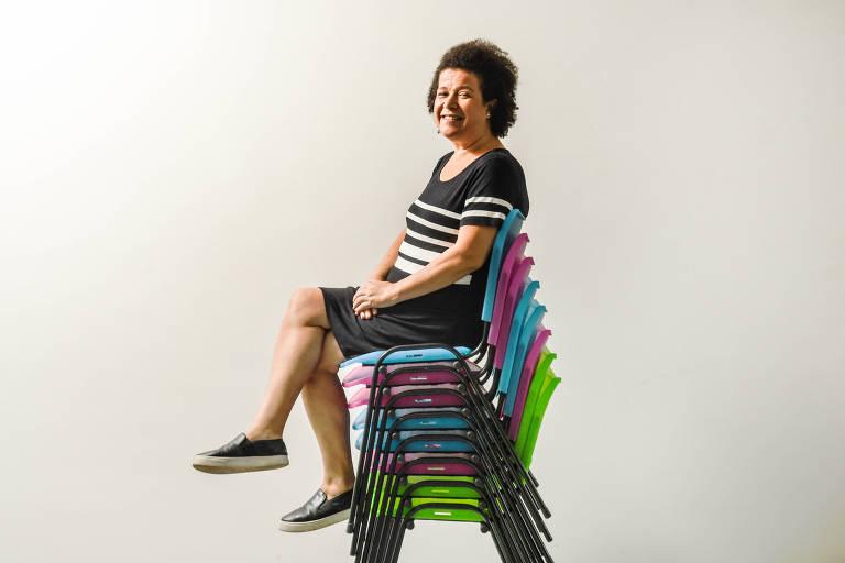 Ana Fontes sentada no alto de uma pilha de cadeiras coloridas