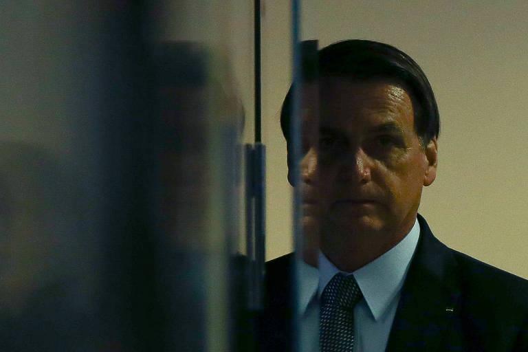 O presidente Jair Bolsonaro, no Palácio do Planalto, nas sombras, perto de um espelho