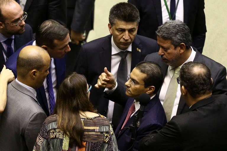 O deputado Arthur Lira (de mão estendida), do centrão, conversa com o líder do governo, Major Vitor Hugo (à esq., de paletó cinza), durante votação da MP 870 na noite de quarta (22)