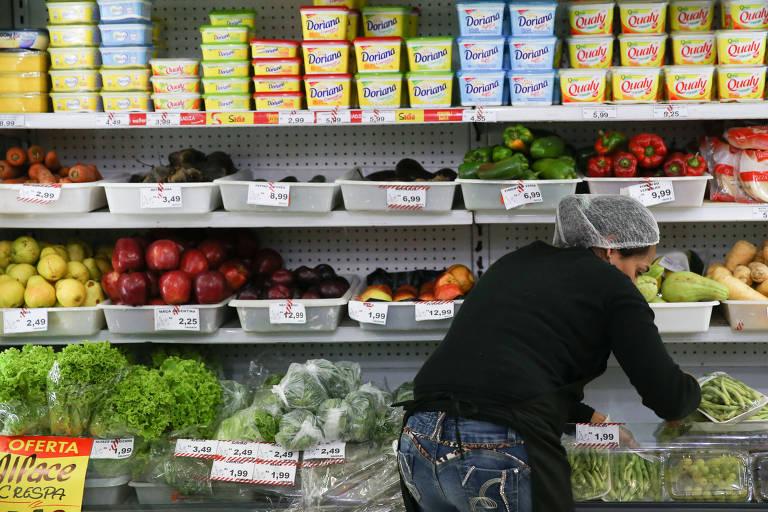 Funcionária abastece gôndola de supermercado em São Paulo