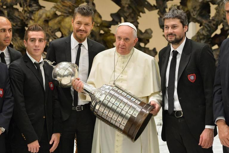 Cercado por dirigentes do San Lorenzo, o papa Francisco segura o título da Copa Libertadores de 2014, vencido pelo time argentino