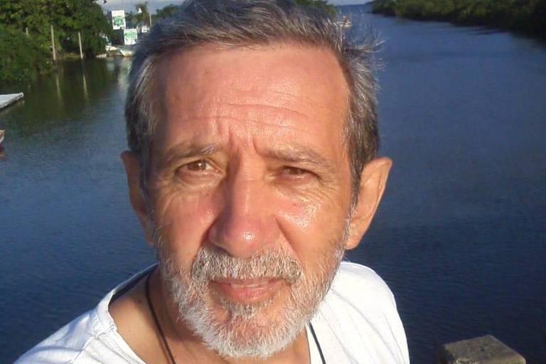 A foto mostra um senhor de 61 anos vestindo uma camiseta branca em frente ao mar