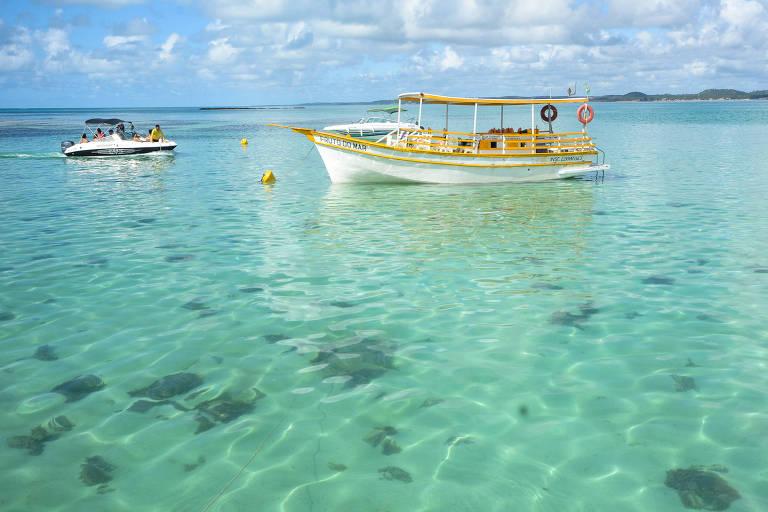 Barco flutua sobre mar cristalino