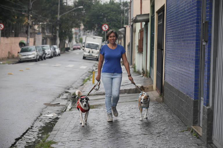 Mulher com roupa blusa azul e calça jeans, ao centro, caminha por calçada com dois cachorros