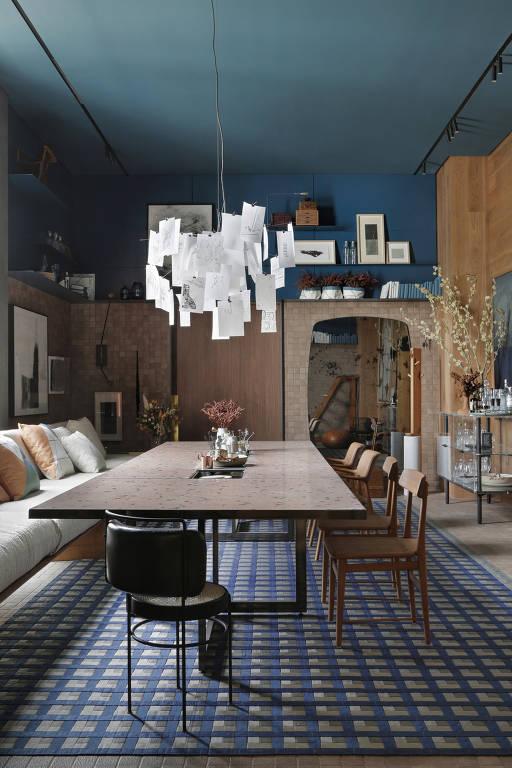Sala de jantar com mesa rosada e paredes nas cores bege e azul escuro