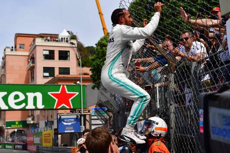 Hamilton sobe alambrado para comemorar sua pole no GP de Mônaco de F-1