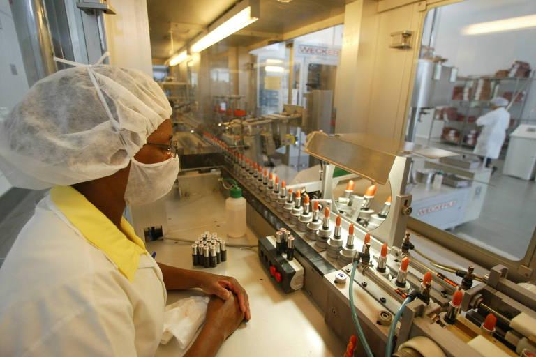 Mulher trabalha na linha de produção de batons na fábrica da Natura em Cajamar, interior de São Paulo