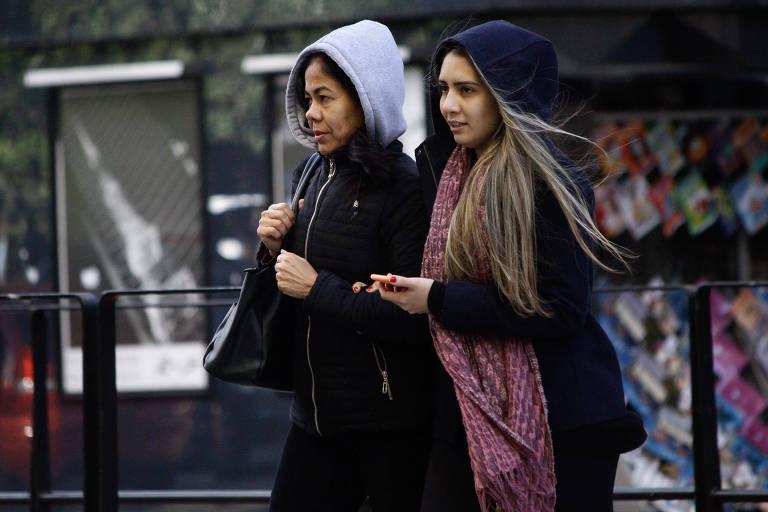 Duas mulheres andam na rua com blusas de capuz