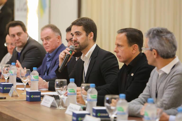 O governador do Rio Grande do Sul, Eduardo Leite (PSDB), fala ao microfone, com o governador de São Paulo, João Doria (PSDB), à direita