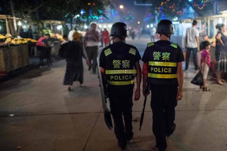 Policiais patrulham uma feira em Kashgar, região chinesa em que tecnologia é usada para monitorar em massa de uigures e outras etnias