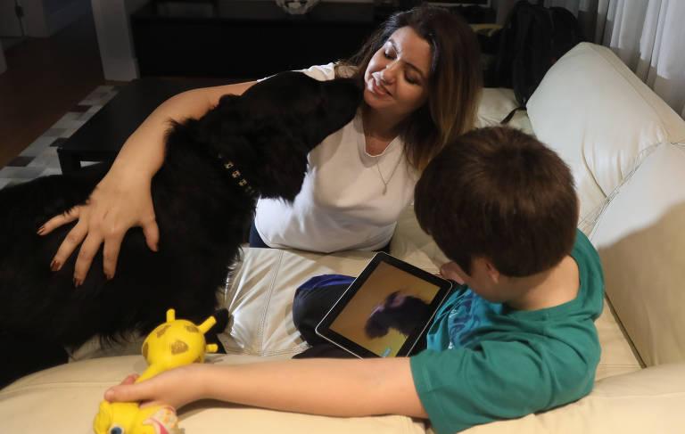 Mulher, criança e cachorro sobre o sofá