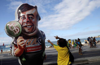A woman gestures next to an inflatable doll, depicting Lower House President Rodrigo Maia, during a pro-government demonstration near Copacabana beach in Rio de Janeiro