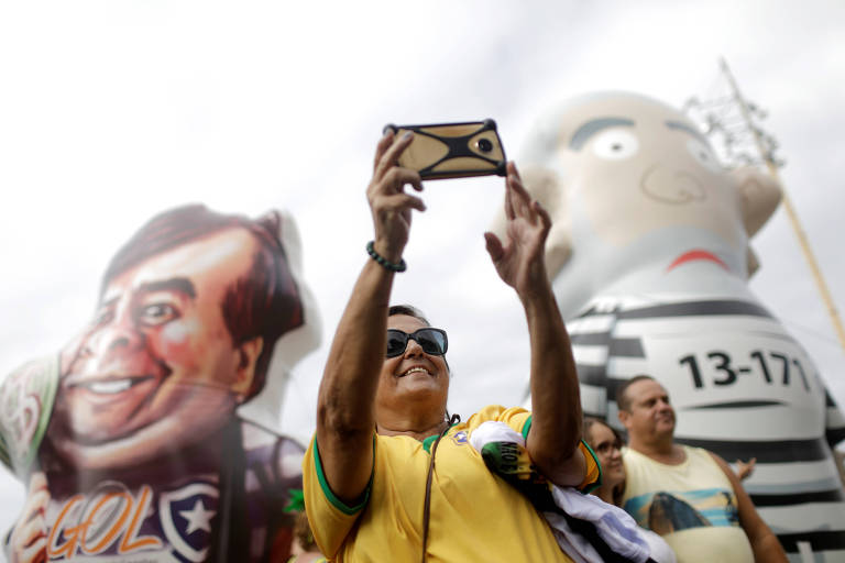 Manifestante tira selfie na frente de bonecos infláveis representando Rodrigo Maia e o ex-presidente Lula