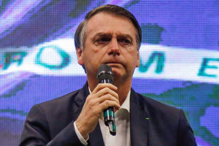 O presidente Jair Bolsonaro durante culto no domingo em igreja evangélica no Rio ; ao fundo, bandeira do Brasil