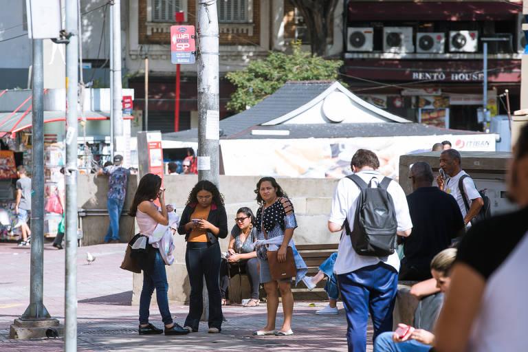 Quatro pedestres usam wi-fi na praça da Liberdade, na região central da capital