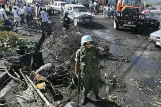 A Brazilian UN peacekeeper stop traffic as removes a barricade in Port-au-Prince