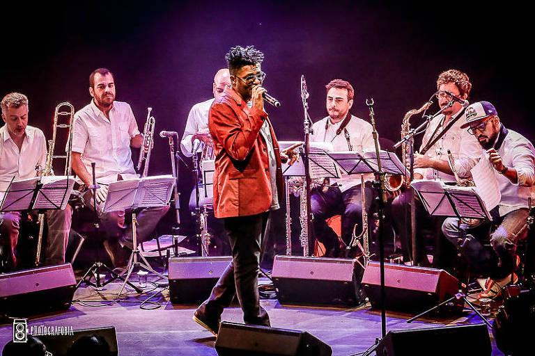 Liderados por Gabriel Moura (em pé, de óculos escuros, calça preta e terno vermelho, e segurando microfone no centro do palco), músicos da banda Orquestra Saga se apresentam ao vivo. Os instrumentistas estão sentados, vestidos de branco e seguram seus instrumentos de sopro atrás de partituras de música