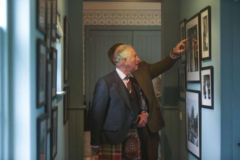 príncipe charles observa fotos na parede da pousada