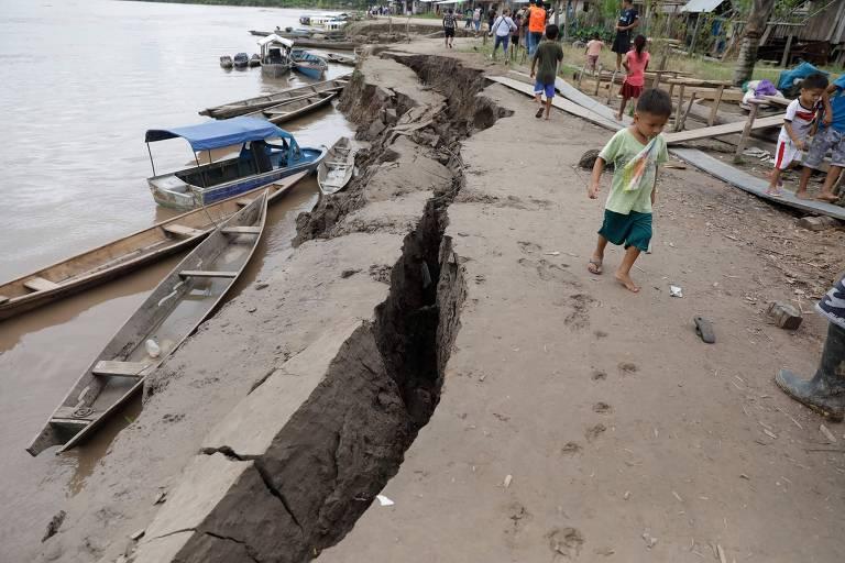 Criança próximo a fenda aberta após o terremoto em Puerto Santa Gema, na Amazônia peruana
