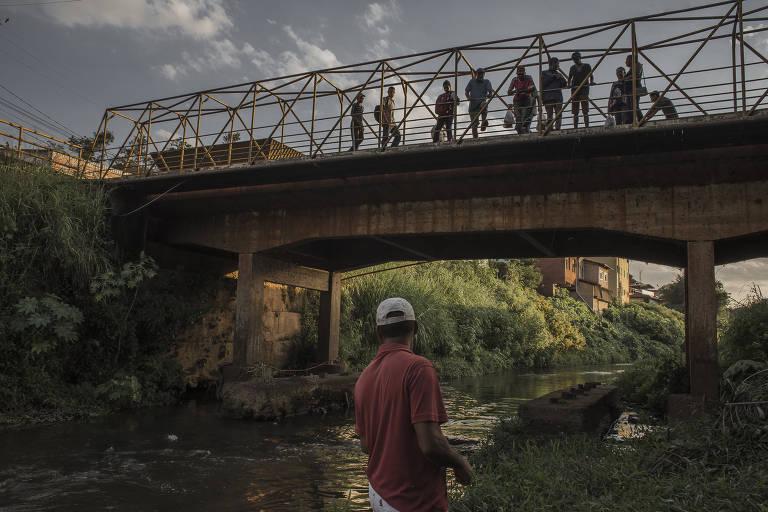 Homem observa, embaixo de uma ponte, rejeitos de minério em um rio