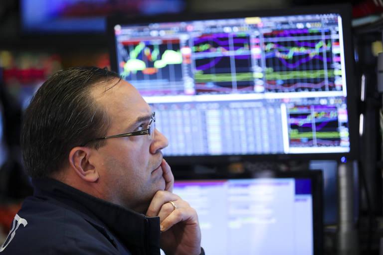 Operador e telas com gráficos da Bolsa de Valores de Nova York