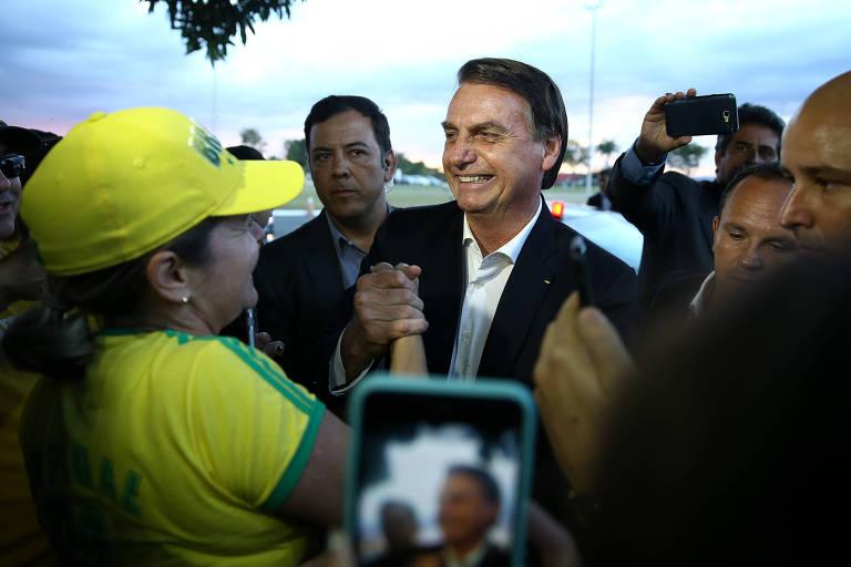 O presidente Jair Bolsonaro (PSL) cumprimenta apoiadores ao chegar no Palácio da Alvorada, em Brasília