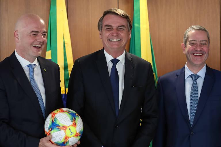 Presidente da República, Jair Bolsonaro, ao lado de Gianni Infantino, Presidente da Fifa (à esq.), e de Rogério Caboclo, Presidente da CBF