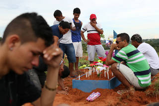Relatives and friends of inmate, Cleison Silva do Nascimento, 25, react during his burial in Manaus