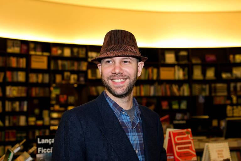 De chapéu marrom, paletó preto e camisa xadrez nas cores preta e azul, cantor Roberto Seresteiro posa para foto. Ao fundo, uma extensa prateleira de livros, na Livraria da Vila, do Shopping Pátio Higienópolis