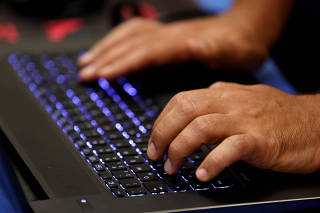 FILE PHOTO: A man types into a keyboard during the Def Con hacker convention in Las Vegas