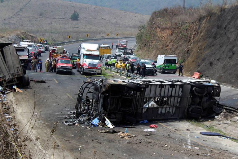 imagem de curva em estrada mostra onibus capotado e queimado; ao fundo, veiculos bloqueiam a estrada