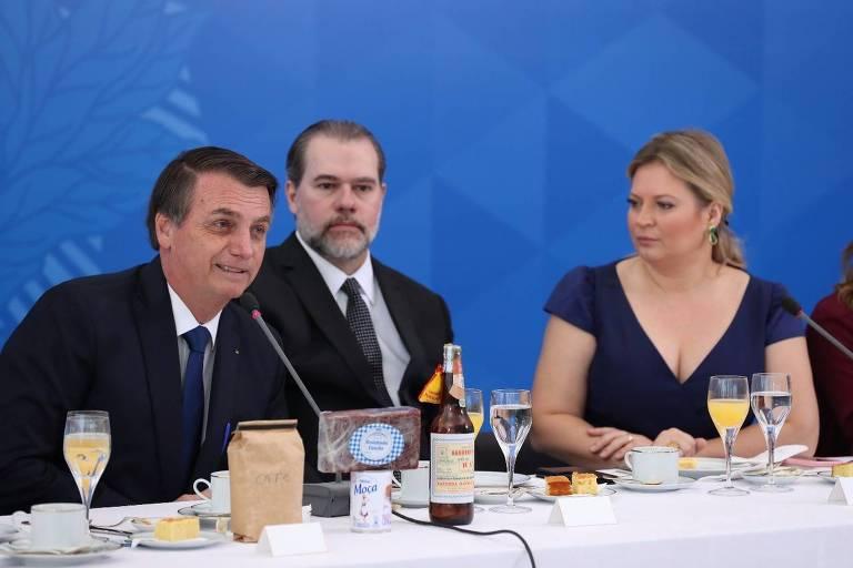 Dois homens de terno e uma mulher de vestido sentados em mesa de café da manhã