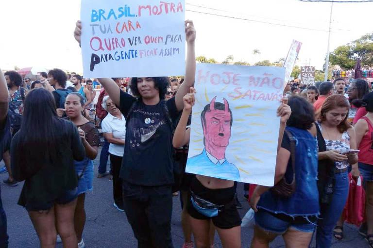 Manifestantes seguram cartazes em protesto no Recife