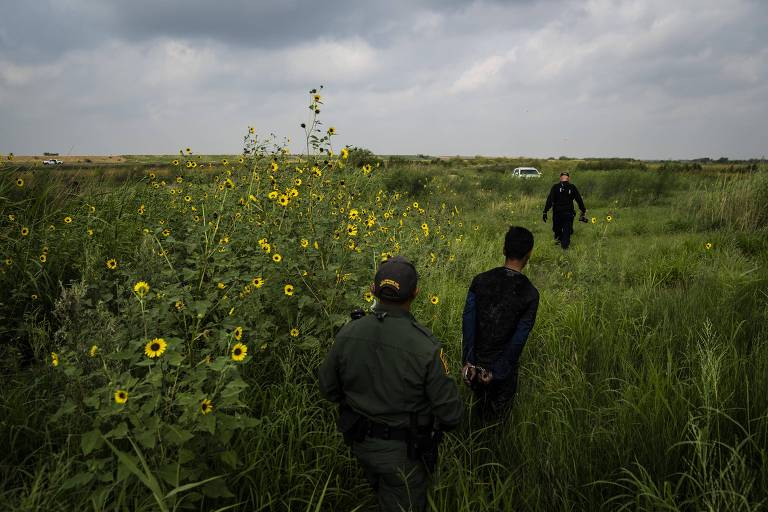 U.S. Customs and Border Protection agents apprehend a 15-year-old boy who was found in a drainage ditch after crossing into the United States from Mexico on Wednesday in McAllen, Texas. MUST CREDIT: Washington Post photo by Jabin Botsford.