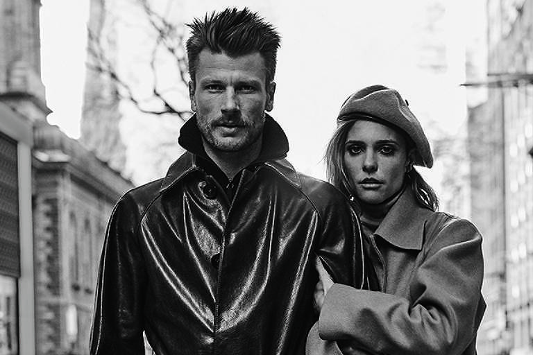 Rodrigo Hilbert posa ao lado de Fernanda Lima em Nova York para ensaio de revista masculina. Fernanda de braços dados com Rodrigo. Eles vestem roupas de frio e estão sérios.