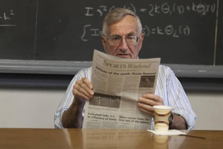 O jornalista Seymour Hersh está sentado em uma mesa de madeira com uma lousa atrás. Ele está de camisa com manga dobrada, lê um jornal e há um copo em sua frente, sobre a mesa