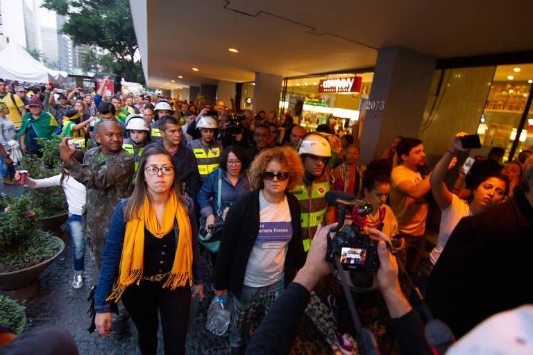 Mulher usando camiseta em homenagem à Marielle Franco é escoltada por policiais enquanto manifestantes bolsonaristas a hostilizam e tentam agredir.
