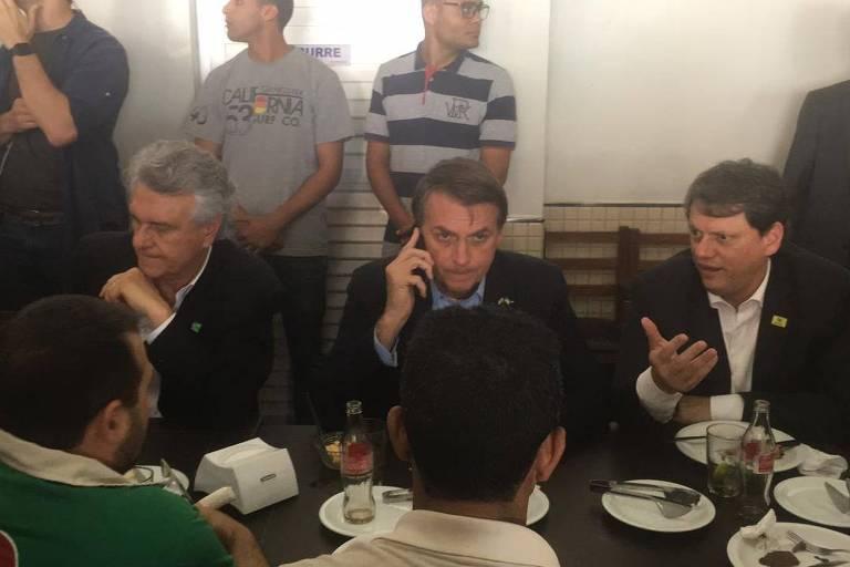 O presidente Jair Bolsonaro (PSL) durante almoço com caminhoneiros em Anápolis (GO), ao lado do governador de Goiás, Ronaldo Caiado (DEM) e do ministro Tarcísio de Freitas (Infraestrutura)