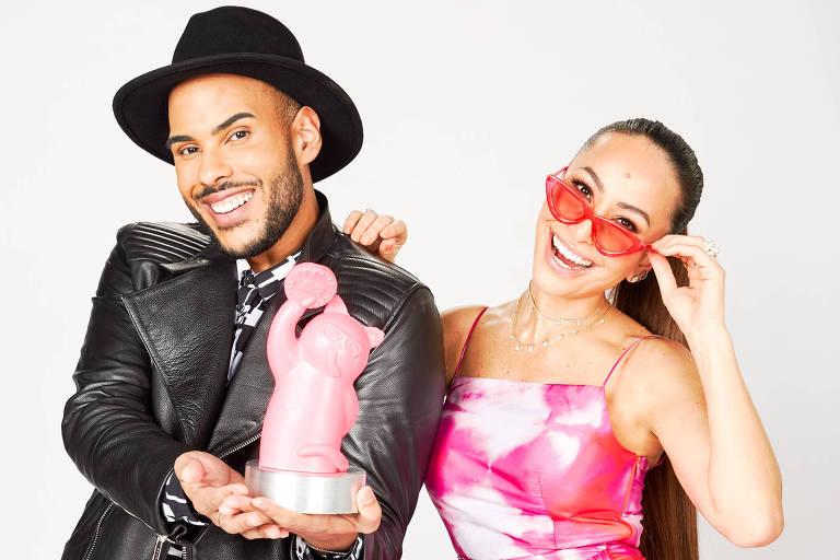 Hugo Gloss está de pé, de braços cruzados, ao lado de Sabrina Sato, que está apoiada no ombro dele. Hugo usa jaqueta de couro e Sabrina um vestido de festa em tons de rosa.