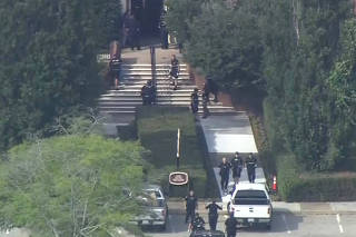 Police evacuate people from a building as a stretcher stands by in this still image taken from video following a shooting incident at the municipal center in Virginia Beach