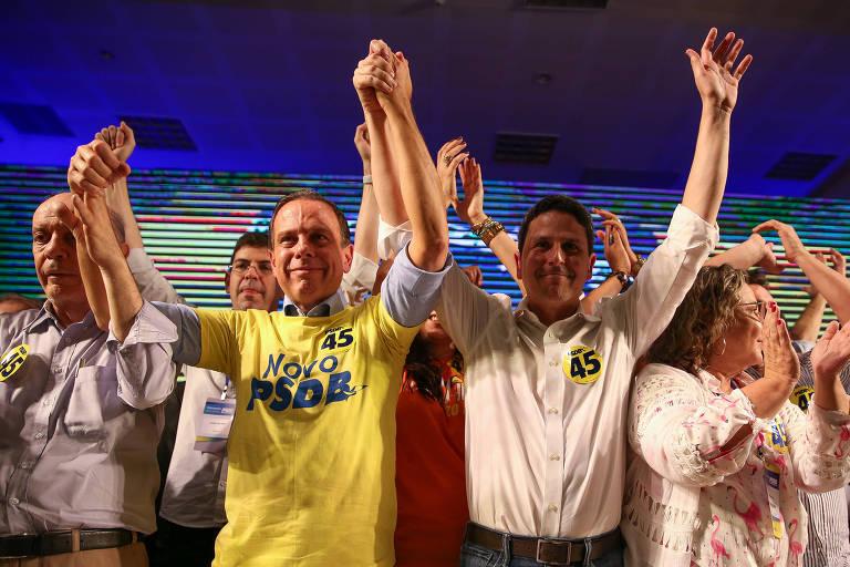 """O governador de São Paulo, João Doria, ergue os braços do senador da """"velha guarda"""" tucana José Serra (esq.) e do novo presidente do PSDB e seu aliado, Bruno Araújo"""