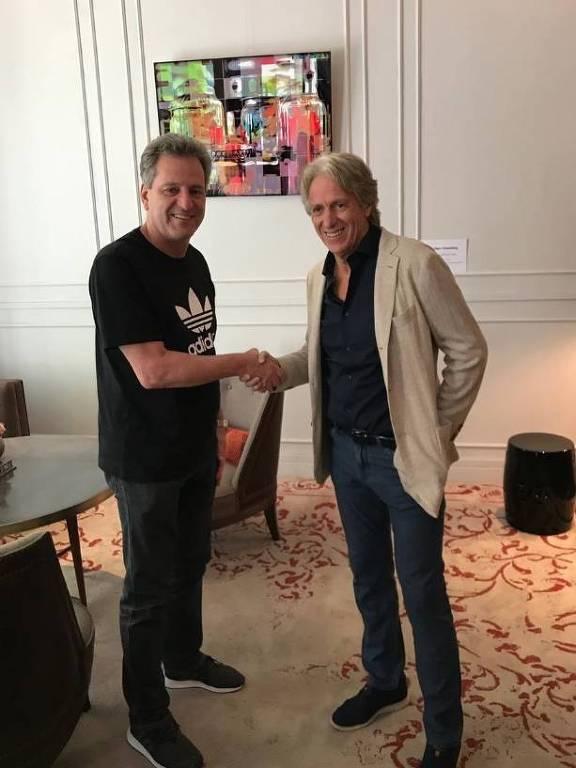 Dois homens, em pé, apertam as mãos