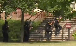 Police enter a building in this still image taken from video following a shooting incident at the municipal center in Virginia Beach