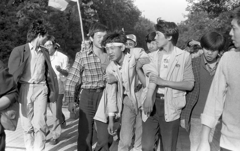 Pessoas ajudam estudante ferido durante protestos na praça da Paz Celestial, em 1989